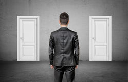 A businessman with his back turned stands between two identical closed white doors. Stock Images