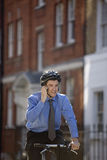 A businessman on his bicycle, talking on his mobile phone Royalty Free Stock Photo