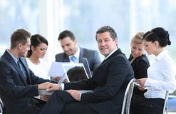 Businessman and his business team with financial documents sitting at a Desk in the lobby of the Bank. Stock Image