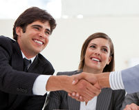 Businessman and his colleague closing a deal. Smiling businessman and his colleague closing a deal with a partner in a meeting royalty free stock photos