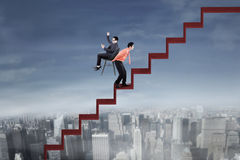 Businessman with his colleague on the red stair. Portrait of success businessman using cellphone and sitting on the chair while his employee lifting a chair on Stock Photos