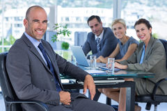 Businessman with his colleagues behind Stock Photos