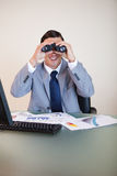 Businessman at his desk looking through binoculars Stock Photography