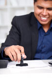 Businessman at his desk stamping. Young businessman at his desk stamping document Royalty Free Stock Images
