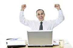 Businessman at his desk on white background. Happy businessman raising his arms sitting at his desk isolated on white background Stock Photo