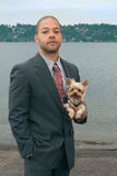 Businessman with his Dog. A young successful businessman and his Yorkshire terrier dog on the lake shore Royalty Free Stock Images
