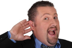 Businessman with his hand to his ear Stock Image