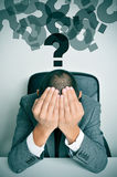 Businessman with his hands in his head and question marks Royalty Free Stock Images