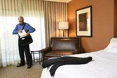Businessman in his hotel room packing his bag royalty free stock photo