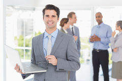 Businessman with his laptop and his colleagues behind Royalty Free Stock Photos