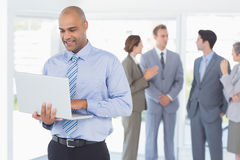 Businessman with his laptop and his colleagues behind Royalty Free Stock Images