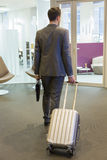 Businessman with his luggage in entrance office. Nomad worker arriving at the office lobby Royalty Free Stock Photo