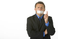 Businessman With His Mouth Taped Shut. And Pointing royalty free stock image