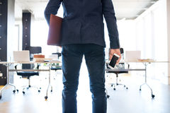 Businessman in his office with smartphone and briefcase. royalty free stock images