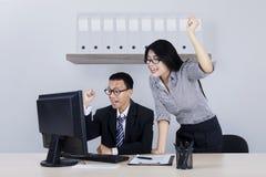 Businessman and his partner lifting hands Stock Photos