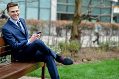 Businessman with his phone on the bench Royalty Free Stock Photography