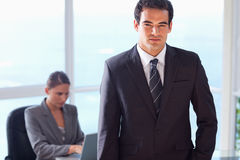 Businessman with his secretary behind him Stock Image