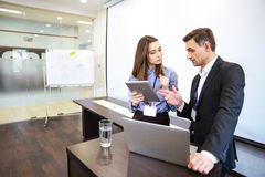 Businessman and his secretary planning work in office. Businessman and his secretary standing and planning work in office Royalty Free Stock Images