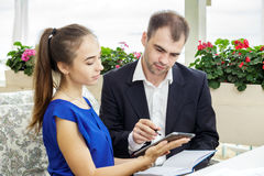 The businessman and his secretary working together. Man makes notes in a diary. Woman showing him something on a tablet. The men in a suit and a white shirt Stock Photo