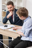 Businessman with his son drawing on business papers Stock Photo