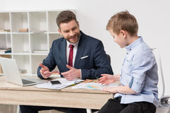 Businessman with his son drawing on business papers Stock Photography