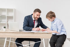 Businessman with his son drawing on business papers Stock Images