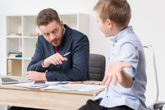 Businessman with his son drawing on business papers Stock Photos