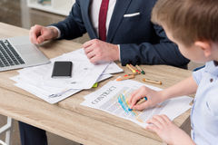 Businessman with his son drawing on business papers Royalty Free Stock Images
