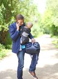 Businessman with his son in a sling talks on the smartphone. And try to opens up a backpack with documents Stock Image