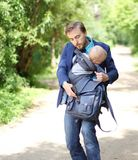 Businessman with his son in a sling try to opens up a backpack w. Ith documents, front view Royalty Free Stock Images
