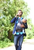 Businessman with his son in a sling walks and talks on the smart. Phone, front view Stock Photography