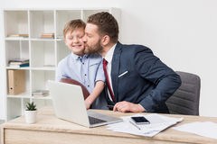 Businessman with his son at table stock photography