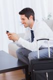 Businessman with his suitcase using mobile phone smiling Stock Photos