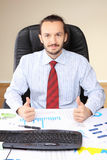 Businessman at his workplace hold thumbs up Stock Photo