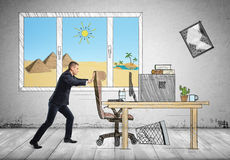 Businessman at his workplace with pyramids and sands behind the window pushing a chair Royalty Free Stock Images