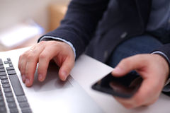 Businessman at his workplace uses a smartphone and Royalty Free Stock Photos