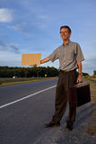 Businessman hitchhiking to work. With a blank sign Royalty Free Stock Image