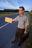 Businessman hitchhiking to work. With a blank sign Royalty Free Stock Photos