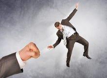 Businessman hitting little man Stock Photo