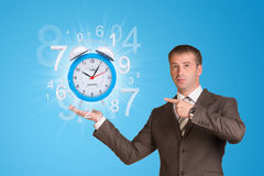 Businessman hold alarm clock with figures Stock Photo
