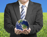 Businessman hold ball with global map with meadow and sky Royalty Free Stock Image