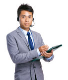 Businessman hold clipboard with headset Royalty Free Stock Image