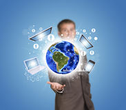 Businessman hold Earth with electronics, graphs Stock Photos