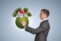 Businessman hold Earth with small house and trees Stock Photos