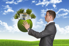 Businessman hold Earth with small house and trees Royalty Free Stock Images