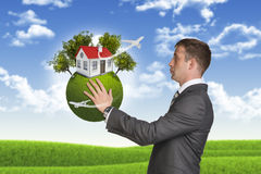 Businessman hold Earth with small house and trees Stock Photography