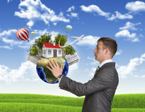 Businessman hold Earth with small house and trees Stock Image