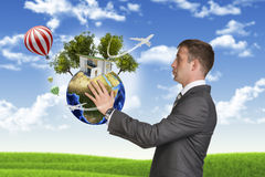 Businessman hold Earth with small house and trees Royalty Free Stock Image
