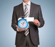 Businessman hold empty card and alarm clock Royalty Free Stock Images