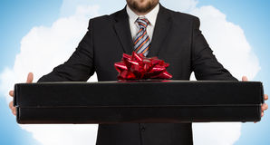 Businessman hold gift box . Mixed media Stock Images